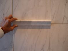 A Bianco Venatino Marble Chair Rail, held against the showroom install of Classic Marble HD Porcelain