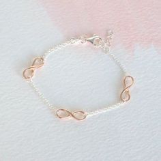 A simple and elegent sterling silver and rose plated bracelet.  Infinity is forever. Be it your friendship or love, let them know that its for always. Three infinity symbols plated in rose gold are linked by sterling silver chain. This modern design allows the sentiment of the bracelet to really shine through. A gorgeous bracelet that comes in a gift box ready to give .  made from: Sterling Silver  dimensions: Adjustable between 17-19cm  * * * * * * * * * * * * * * * * * * * * * * * Delivery…