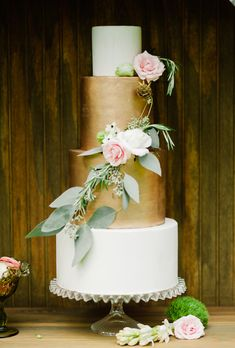 Brides.com: 29 Glam Metallic Wedding Cakes A four-tiered wedding cake with two gold tiers and draped flower details, from Earth and Sugar.Photo: Merari Photography