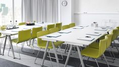 Conference room with white desks and green leather chairs