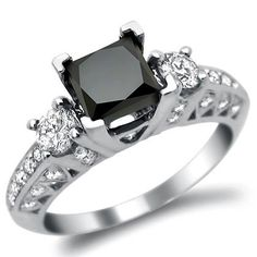 Black Princess Cut 3 Stone Diamond Engagement Ring - Here's a beautiful 2.25 carat multi-color Black Princess Cut 3 Stone Diamond Engagement Ring set in 18k White Gold. It features a very excellent AAA quality 1.40 carat solitaire Black Princess Cut diamond set atop the item. It also has .85 carats of White Brilliant Round Diamonds that surround the solitaire. They are set down each side of the ring, the front & back. It measures 7mm wide. All diamonds are 100% natural…