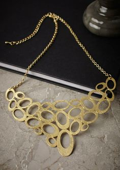 GOLD CIRCLES STATEMENT NECKLACE £23.95 This lovely Gold circles statement necklace features a number of circular scratched finish pieces.