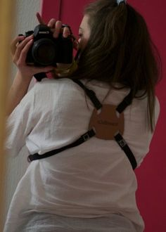 While a camera harness looks somewhat like a lunchbox, it is one of the most comfortable ways to wear a camera. The harness not only takes the weight of your neck (and places it like a backpack on your shoulders and back), it also prevents the camera's from swinging into each other or other things in front of you. The really nice stuff comes from Lowepro, but if you are willing to get your hands dirty you can make a simple one yourself. Chiara Sciarone explains just how to make one: