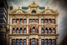 FAR MORE ORNATE Melbourne, Victoria, Australia. The top few floors of 258 Flinders Street in Melbourne provides an indication of the architectural beauty of this city at the end of the 1800's.  The red bricks and the cream rendered features are far more ornate than todays buildings and must have taken considerably longer to build than the formed concrete that we see now.  I love this type of photography, but it is getting harder to take with power lines, cars and people all conspiring to ...