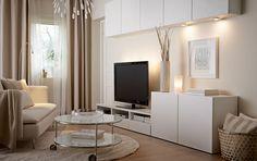 En stue med hvide vægskabe, hvidt tv-bord og hvide skabe