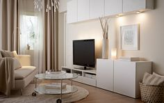 A living room with wall cabinets, TV bench and cabinets, all in white