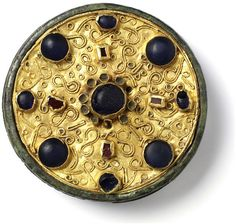 Large gold disks brooches are the most characteristic creations of seventh century Frankish goldsmiths work and are usually set with glass and or semi-precious stones. The brooch is also adorned with filigree (twisted threads of gold applied to the surface) Certain designs in the filigree on Frankish brooches, such as the S shape, elaborated into the figure eight on the present example, show continuation of Roman decorative tradition.