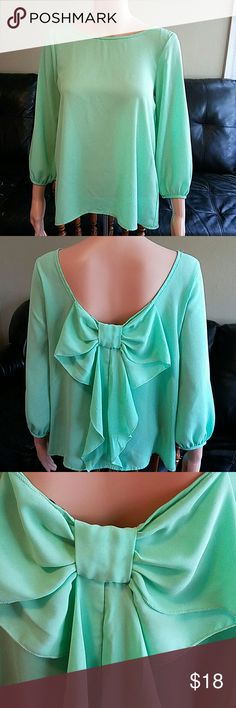 Bow back mint green silky 3/4 sleeve shirt This shirt has been worn but as an excellent preowned condition. The best measures at 18 and a half inches across and the length is 23 inches. This is a silky like polyester material and there is no stretch. This leaves or 3/4 length. Necessary Clothing Tops Blouses