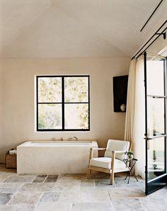 A restrained bathroom featuring a 1940s René Gabriel chair.