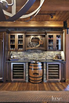 Blending rustic elements with modern conveniences, the bar area in the kitchen features custom cabinetry, dual wine refrigerators by true and a sink basin made from an antique whiskey barrel. distinctive stone installed the backsplash.