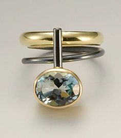 Janis Kerman: Blue Topaz Ring, Ring in sterling silver, 18k gold and blue topaz (stone is approx 10mm at widest point). Size 6 1/4.
