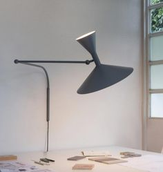 Designed by Le Corbusier for the Unité d'Habitation of Marseille in 1949/1952, it is an adjustable wall lamp with two joints on the arm and a rotating wall fixing. Spun aluminium diffuser. Available with matt grey or whitewash body, with white internal diffusers. Direct and indirect lighting output. Double switch on the cable, for a functional and adjustable light output.