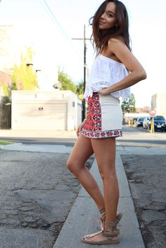 Ashley Madekwe is wearing an embroidered top and embroidered A-line skirt from Topshop and sandals from Isabel Marant