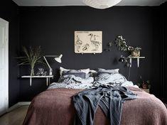 Een zwarte muur en veel planten in de slaapkamer. Dit appartement bewijst dat die combinatie ontzettend fijn samen gaat!