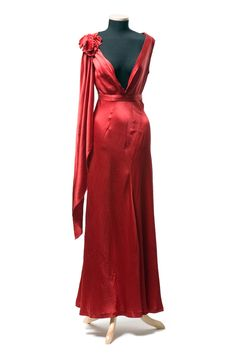 Red rayon evening gown, 1930s. Cut very low in front and high in back, with large velvet flower on right shoulder. Bias-cut gored skirt. Worn by Elizabeth Woodroe Meadows (1903-1992) of Charleston, West Virginia. The bias cut was devised by French couturier Madeleine Vionnet in the 1920s, cutting across the grain to add draping and stretch to any fabric. Usually, a woman could step into her dress without the need for side, back or front openings.