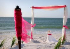 Florida beach wedding style with fuchsia accents on our two post arch