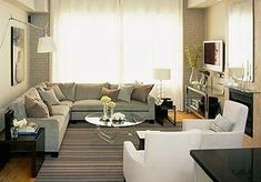 source: Sarah Richardson Design Such a lovely small space.....how apartment-friendly!! Gray sectional sofa, acrylic lucite modern cocktail table, striped rug, white accent chairs and fireplace.