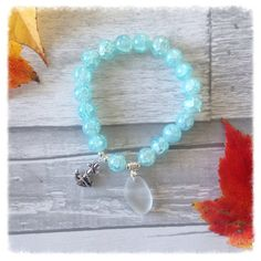 Beautiful aqua bracelet with a white piece of Sea Glass and a charm  This unique piece is a perfect representation of Nova Scotia, Canadas Ocean Playground.  Each piece is 100% unique , made with genuine sea glass. The glass has not been altered in anyway and is exactly as it was picked along the shores of our beautiful coast line. 💙 Made with love 💙