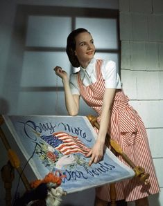 1943 Model in a red and white striped pinafore over a white playsuit.