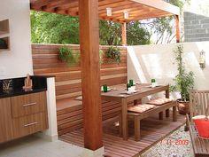 espaço bem aproveitado de churrasqueira com mesa de madeira na área externa da casa.