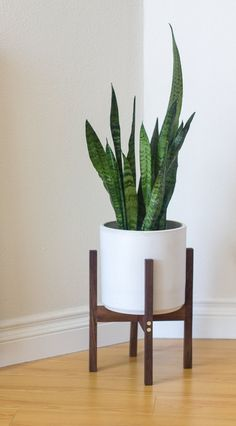Our Small modern planter stands are made from American Walnut hardwood and recycled industrial solid brass rod. Using through dowel construction with a modern brass metal accent, our design puts a high class twist on a classic. Includes cylinder ceramic by PMD in Gardena, CA. Black and White glazes available. Please see other listing to order without ceramic.  - Stand: 8-3/4 internal diameter, 12 height, 10-1/4 width - Ceramic: 8 internal diameter, 8 height - Ceramic on stand: 14 height…