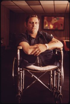 Original Caption: Jack Smith, 42, Rhodell, West Virginia, Seated in the Beer Joint He Operates in a Wheel-Chair Bought for Him by His Friend Arnold Miller, President of the United Mine Workers Union. He Was Disabled at Age 21 after a Year in the Mines and Had to Wait 18 Years to Collect Workman's Compensation. He Stays Current on Union Affairs and Will Man a Picket Line. During the Strike for Black Lung Benefits His Wife Wheeled Him in Front of a Train to Stop It 05/1974    U.S. National Archives' Local Identifier: 412-DA-14034    Photographer: Corn, Jack, 1929-    Subjects:  West Virginia (United States) state  Environmental Protection Agency  Project DOCUMERICA