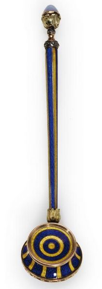 Property from the Collections of Lily & Edmond J. Safra: A rare Fabergé gold and translucent enamel hand seal, St. Petersburg, circa 1900. In the form of a warming pan, enameled with translucent royal blue and yellow stripes over guilloché grounds, the racing colors of Leopold de Rothschild, the long tapered handle with moonstone finial.