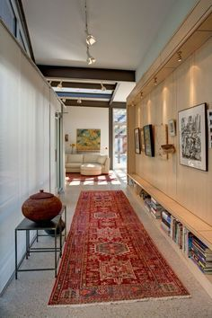 The door opens with just a light push up to a large foyer that the homeowner uses as a gallery space to exhibit her art collection above and her book collection below and her rug collection on the floor.