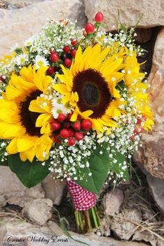Picnic Wedding Theme.  Yellow and red bouquet with yellow sunflowers, red hypericum berries, babies breath and lemon leaf.  Wrapped in red gingham.