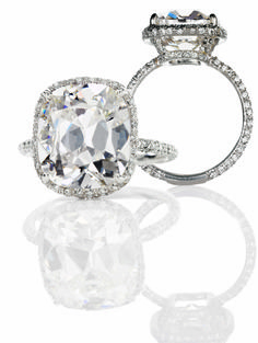 Cushion cut center stone (rounded corners), tiny micro pave halo. Diamonds 3/4 around band and under crown setting. So pretty!