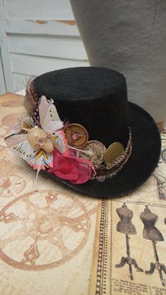 Steampunk Little Black and Pink mini Top Hat -  Feathers Coin Sprockets and Gears Skull Hawkmoth Butterfly. $45.00, via Etsy.