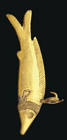 AN EGYPTIAN GOLD OXYRHYNCHUS FISH AMULET   LATE NEW KINGDOM-LATE PERIOD, CIRCA 1150-350 B.C.   The slender fish wearing a triple-beaded collar and a sun-disc between Hathor's horns, the dorsal and caudal fins with details incised, pectoral fins of applied wire, eyes recessed for inlays, now missing  1½ in. (3.9 cm.) long