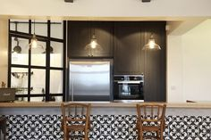 Dry kitchen featuring monochromatic tiles on a peninsula counter and retro furnishings.