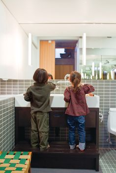 In the bathroom, the twins take advantage of a custom-built Corian sink and wooden base with integrated step when it's time to wash up.    Read more: http://www.dwell.com/slideshows/plays-the-thing.html?slide=9&c=y&paused=true#ixzz1WXFdfNmd