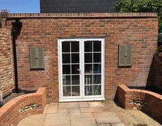 Mirrored brick retaining walls with flint panels Retaining Walls, Brickwork, Garden Design, Garage Doors, Patio, Mirror, Building, Outdoor Decor, Home Decor