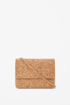 Made from a soft cork material, this compact shoulder bag has a flap-over front and hidden magnetic fastening and is secured with zip-up.…