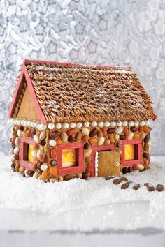 """For this stone cottage, usegum to trim the windows, door frames, and rooftop. Pipe icing in a decorative fashion under the roof eaves. Use brown icing to mortar halved jelly bean """"stones"""" onto the house, and to secure bran cereal pieces to the roof. Dust the roof with confectioners' sugar."""