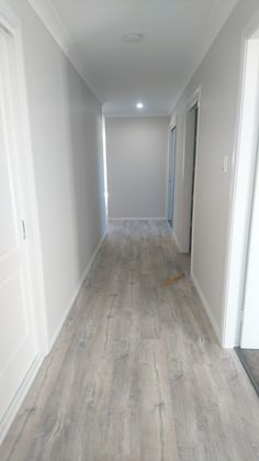 Grey pebble HALF Entrance hallway vinyl planks new home. Might put some large artworks on the left and some neutral tone artwork or charcoal drawing at the end. Dulux paint colour Grey Pebble half with Grey Pebble quarter trim Grey Vinyl Plank Flooring, Luxury Vinyl Tile Flooring, Hallway Flooring, Wood Tile Floors, Kitchen Flooring, Dulux Paint Colours Grey, Hallway Paint, Grey Hallway, Wood Floor Texture