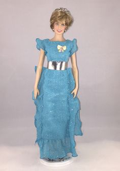 This Franklin Mint Diana doll is wearing a replica of a pale blue evening dress with a broad silver belt by designer Bruce Oldfield that Diana, Princess of Wales, wore for a Dinner Hosted by The Province Of New Brunswick during the Royal Tour of Canada June 18, 1983.