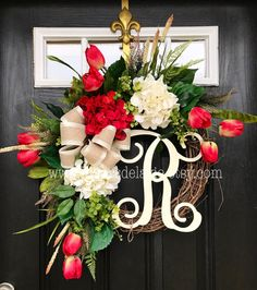 Gorgeous Spring Door Wreath! Perfect for greeting your guests to your home with this one of a kind door wreath.  Made up on an 18 grapevine wreath with moss, mixed flowing greenery of ivies, boxwood, eucalyptus, hydrangeas leaves, ficus leaves and ferns. Beautiful cream and red hydrangeas with white accents and gorgeous red/lime green tulips with a decorative 12 Ivory script monogram and cream satin burlap bow.  This wreath is just stunning!   Measures approx: 28 x 25 x 7( tip to tip)....