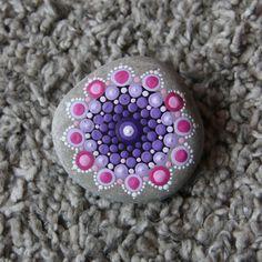 Mandala steen met onder andere paarse en rose tinten. Circa 6,5 cm diameter om een indruk van de grootte te geven. De steen is 149 gram. De mandala steen is afgewerkt met een laagje vernis maar kan alsnog niet gebruikt worden voor buiten, etc. Alle mandala stenen zijn uniek en uiteraard handgemaakt. Op de achterkant van de steen staat mijn naam. De stenen komen uit Duitsland en Frankrijk. Voor het idee ben ik geïnspireerd door Elspeth McLean. Verpakt in een organza zakje met een leuk label…