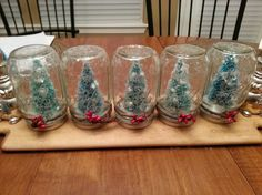 Christmas tree snow globes! GREAT GIFT IDEA!!! Made one for my boyfriend's family and all of my friends! Buy a package of mason jars(local supermarket) and get minuscule trees at craft store. Simply glue tree to bottom of lid, add snow and voila! To jazz up the jar, add twine and some holly berries (also found at craft store).