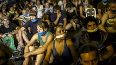 Demonstrators with their mouths taped sit outside the Spanish parliament during a protest against Spanish government's new security law in central Madrid, Spain, early July 1, 2015. Photo:Reuters