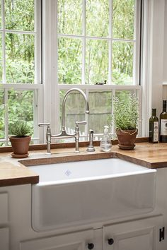 Country Traditional Kitchen: An apron-front sink and wooden countertop in a kitchen.