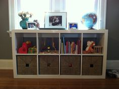 Another version of the Ikea Expedit bookshelf. You'd never know our diaper stash and toys are neatly tucked away in those baskets! Our living room looks ten times better with this orderly addition!