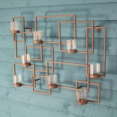 This stylish metal wall art looks equally elegant hung in the home or garden.A modern geometric design, this stylish piece of garden wall art features strong, interlinking metal shapes with 8 glass candle holders to shed a soft, flickering light on your garden wall. Suitable for indoor or outdoor use, this stunning, unique piece would make an ideal gift Measurements: h:<strong> </strong>57cm x w: 42cm (tealight candles not included)<strong></strong>MetalMeasurements: h…
