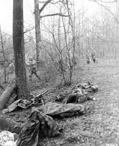 A dead American machine gun crew. Fellow Soldiers move on in the background....