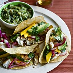 Who's up for MEXICAN tonight? These tilapia tacos are packed with protein, low in fat, and made even more delish with the addition of mango and avocado slices. MMMMM | health.com