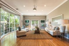 The living room's large floor-to-ceiling bay window offers views from city lights to canyon terrain.