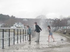 Photograph of kids getting hit by a wave on the Boulevard, Gloucester, Massachusetts . Don't know who took it.